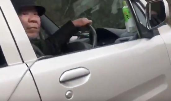 排気ガスを犬に当てる高齢男性の顔画像