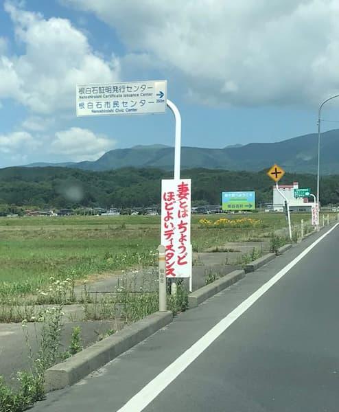 道路の看板「妻とはちょうどほどよいディスタンス、夫とはとっくに心もディスタンス」