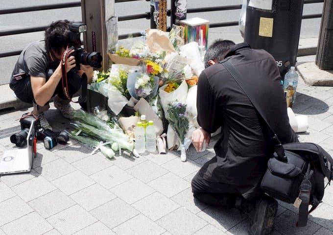 共同通信のカメラマンが献花台の脇にしゃがみこみ祈る関係者の顔を前から撮影。